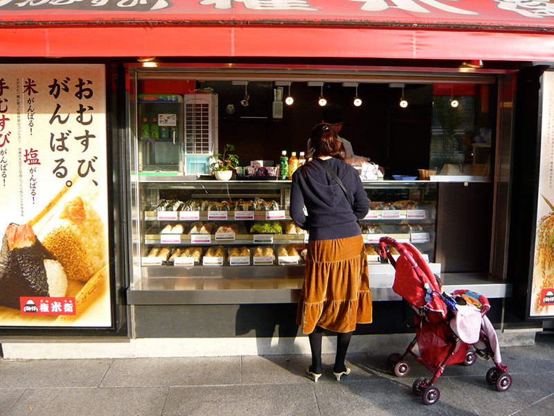 woman standing outside japanese food onigiri stand