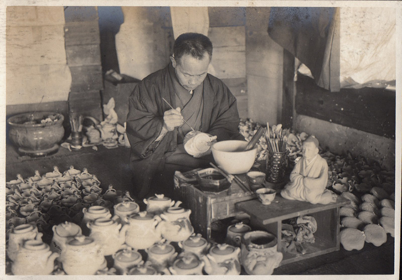 black and white japanese man painting pottery