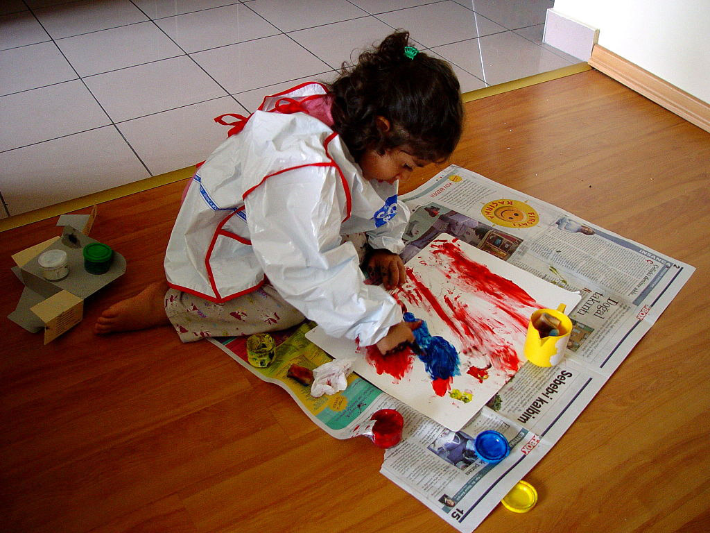 A child finger painting on the floor