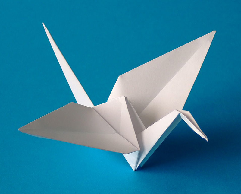 An small origami crane on a blue background
