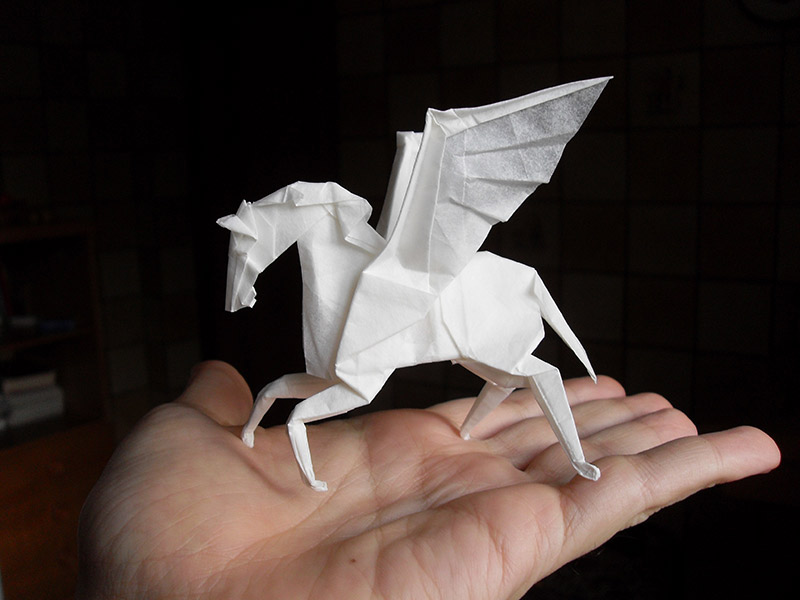 A paper pegasus standing on a person's hand