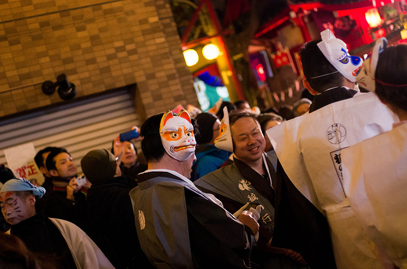 people at a japanese matsuri with fox masks