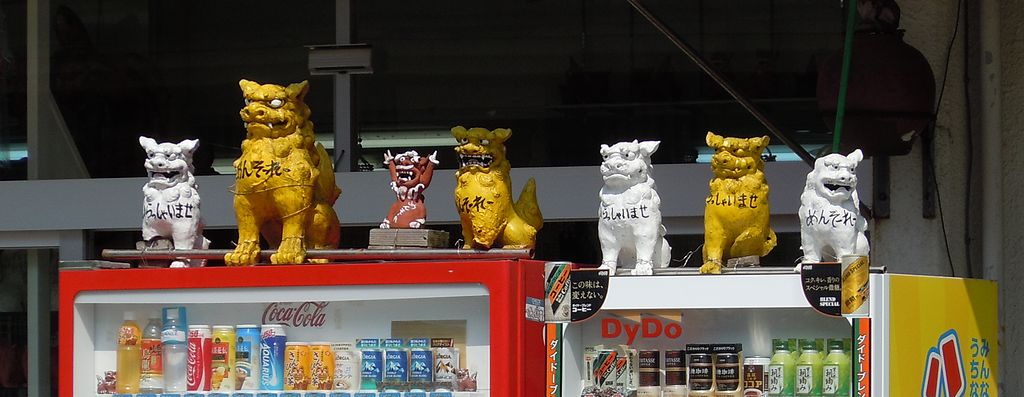 shiisa hanging out on top of vending machines in japan lion dog