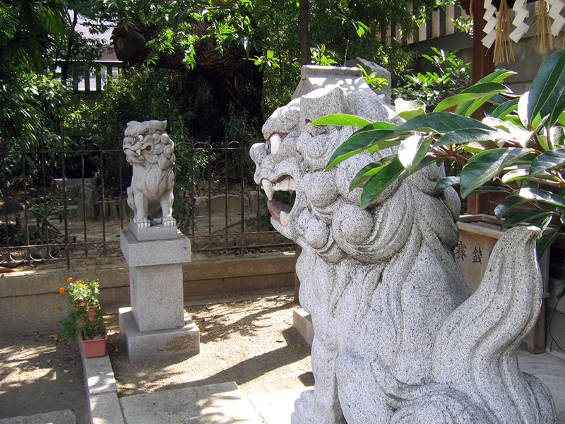 two lion dog statues outside a japanese temple