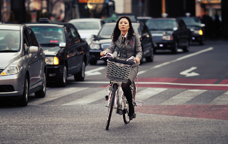 Japanese woman in grey suit riding bike with basket