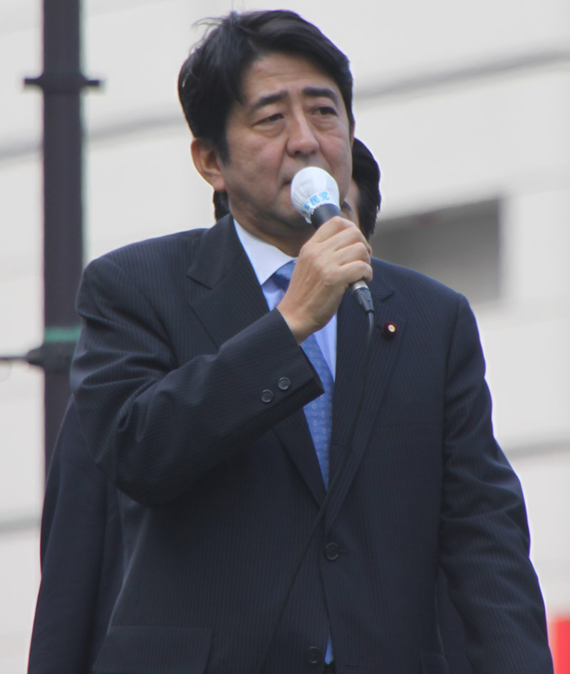 Japanese president shinzo abe talking on a microphone