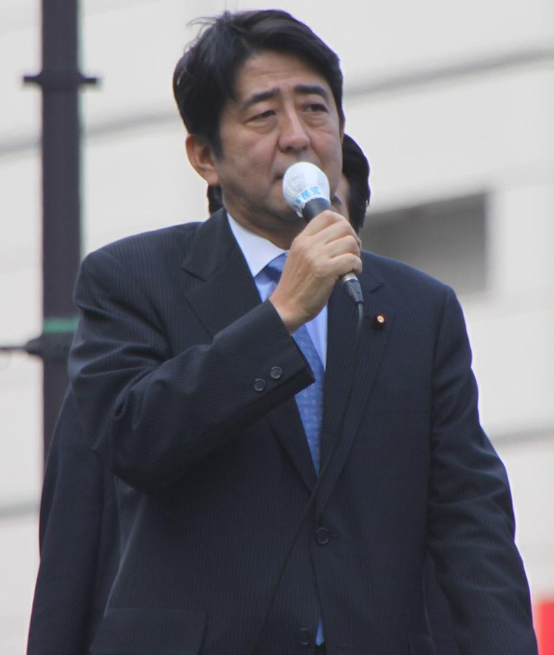 Japanese president shinzo abe talking on a microphone