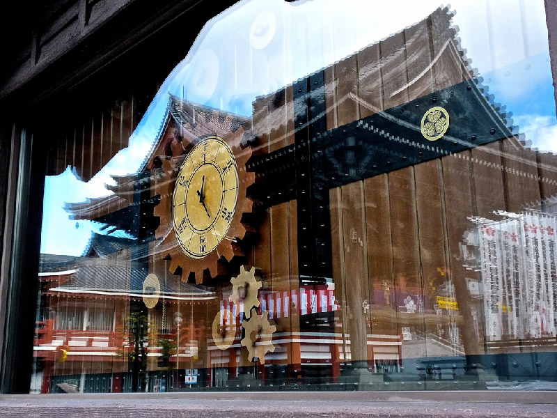reflection in glass of clock shop