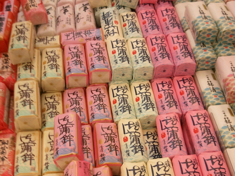 Kamaboko wrapped up in different colors in a shop