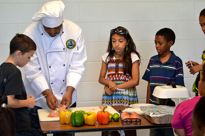 navy chef prepares food with elementary school students