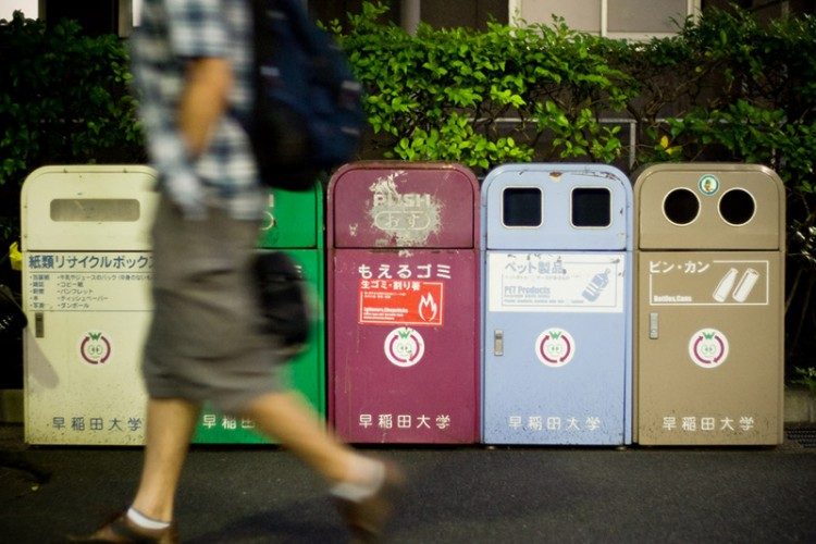 A man walks by five Japanese garbage bins