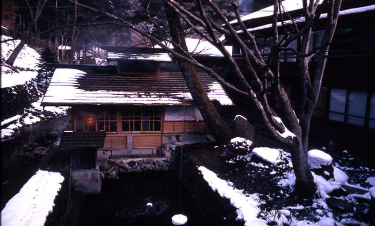 A wooden Japanes-style building by a pond in the snow
