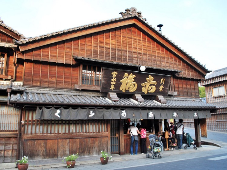 A wooden Japanese building with a short curtain hanging over its entryway