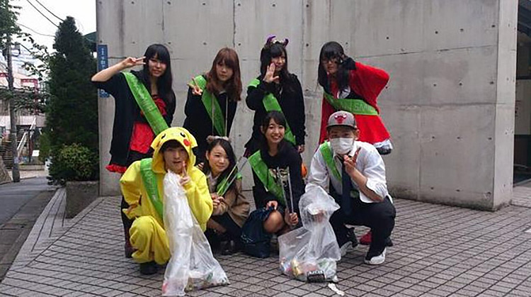 group of japanese people that volunteered to clean up halloween trash