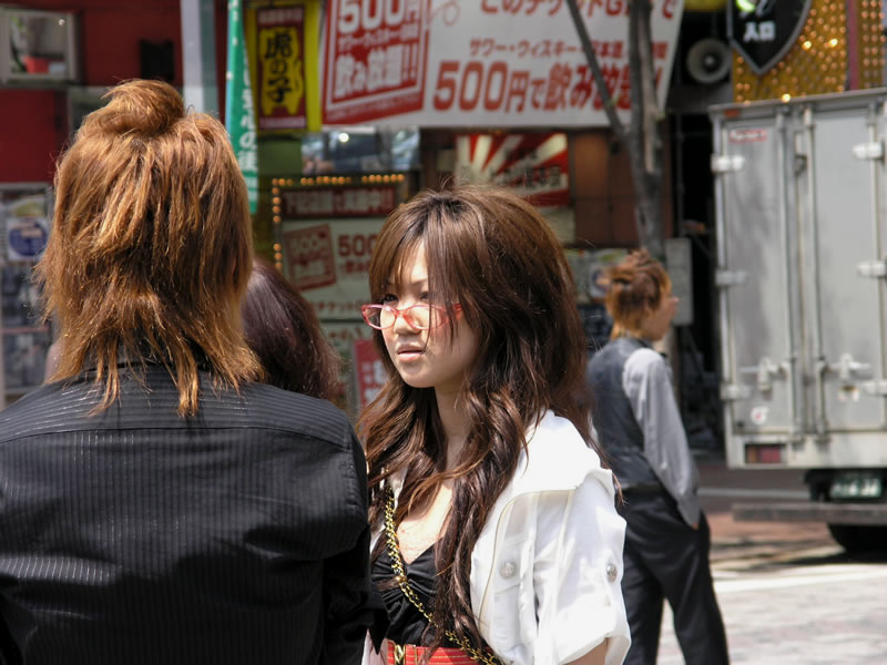 A fashionable gyaru woman with red-framed glasses