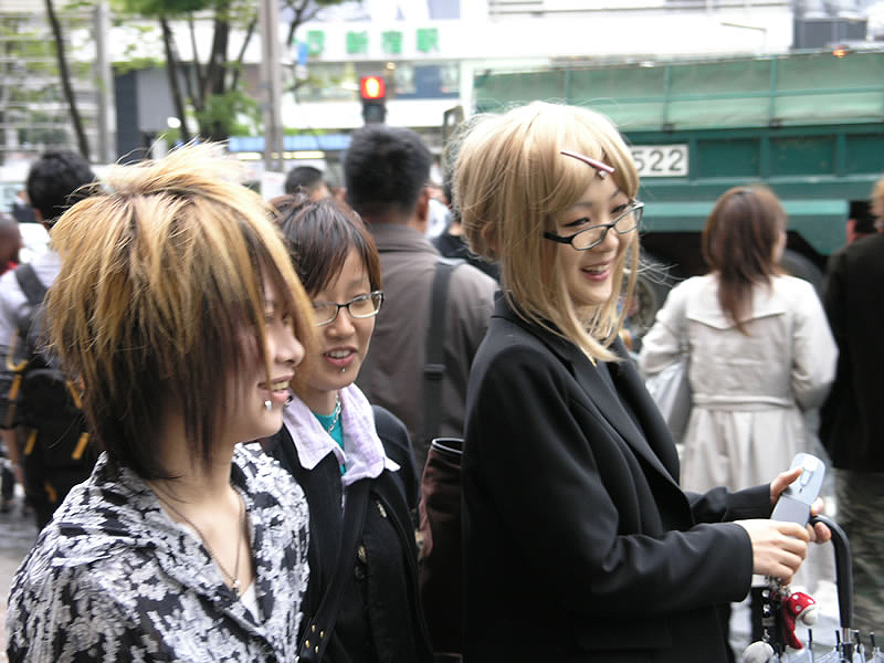 A blond Japanese woman wearing black glasses