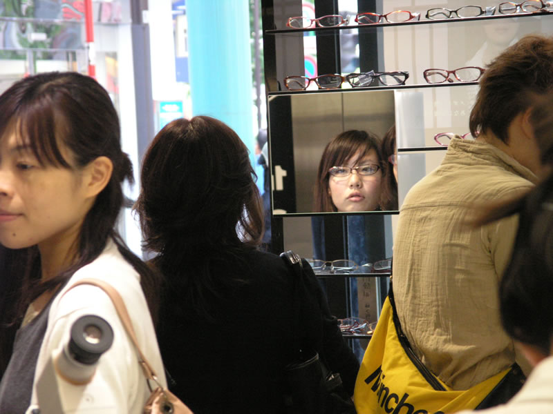 A woman looking in the mirror of a glasses shop