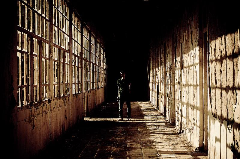 man standing alone in a strangely lit hallway