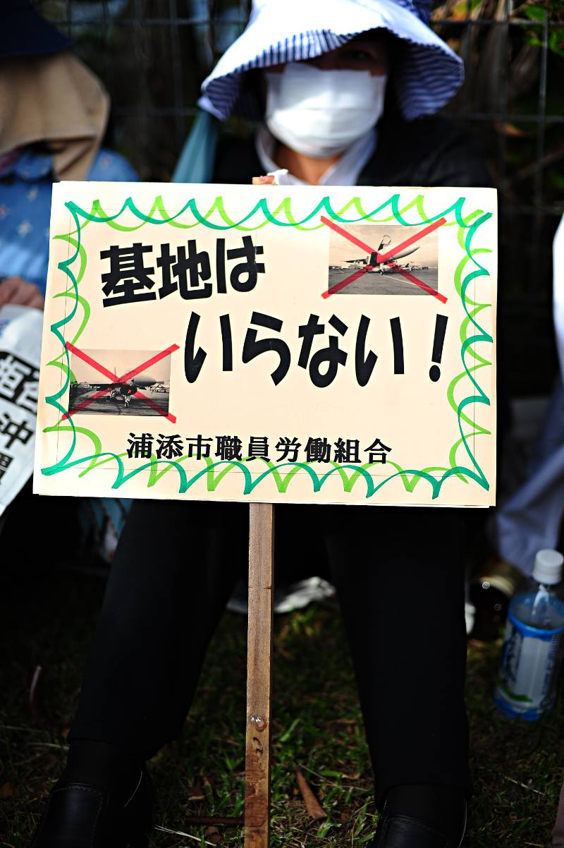 woman holding an anti okinawan base sign