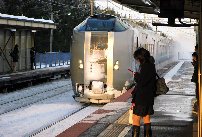 japanese girl at train station on phone in winter