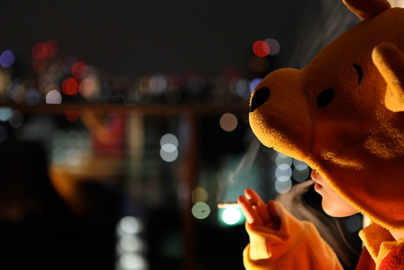 A woman in a Pooh Bear onesie smoking