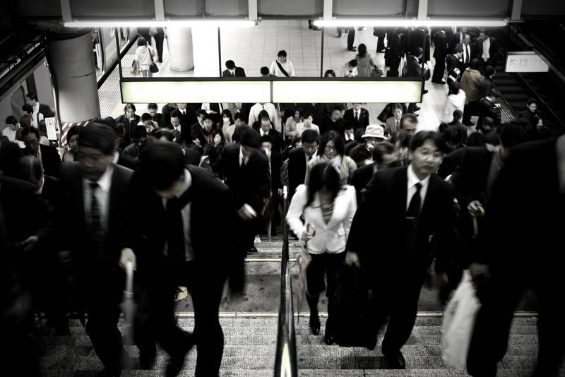 japanese commuters walking up crowded staircase in tokyo train station