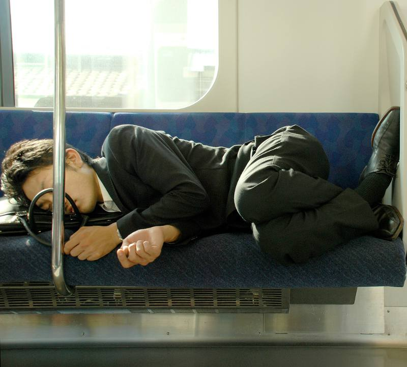 hardworking salaryman in japan sleeping on train seat