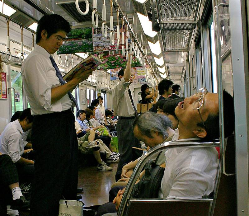 snoring japanese office worker in foreground on busy train