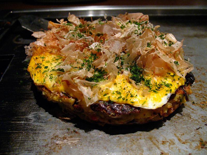 Katsuobushi fermented fish flakes on top of okonomiyaki while cooking