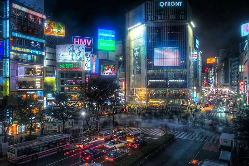 lit up shibuya and billboards intersection in the evening