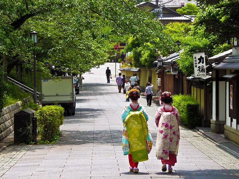 two geisha wearing kimono and walking alone