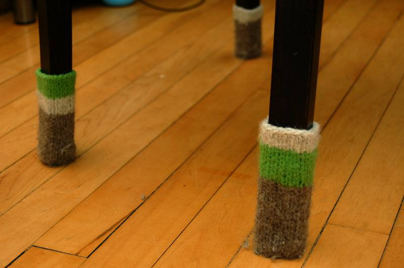 Knitted socks on the bottom of chair legs
