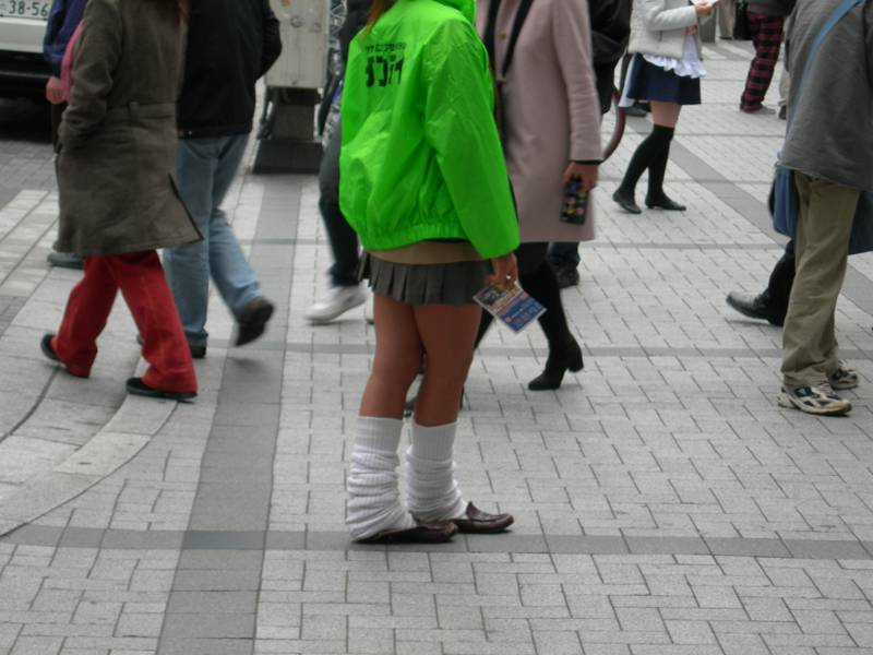 A gyaru woman with very tan legs and slouchy white socks nearly up to her knees