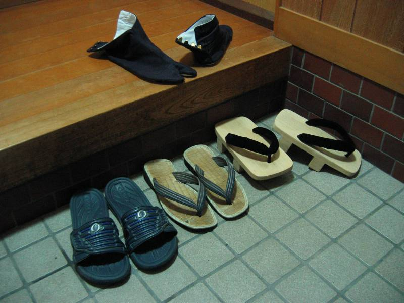 Slippers and geta in an entryway with tabi socks on the step up