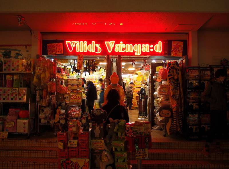 A Village Vanguard storefront at night with the neon shop sign lit up