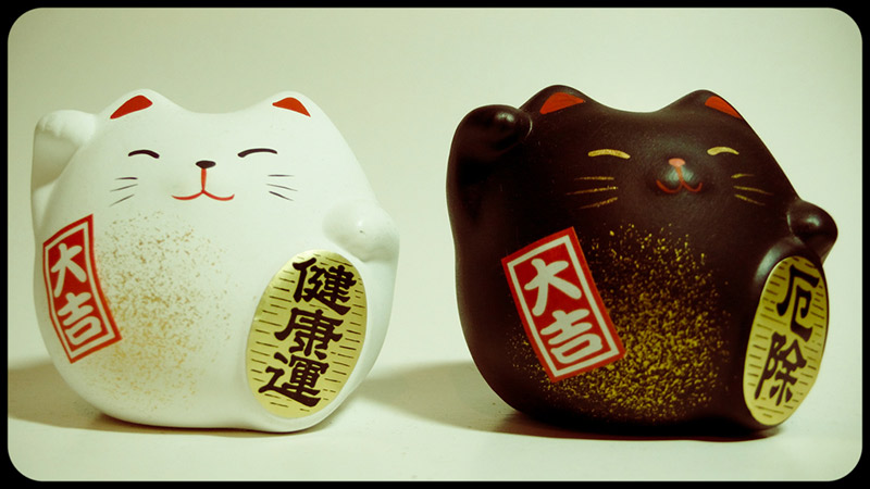 three round lucky cat sculptures