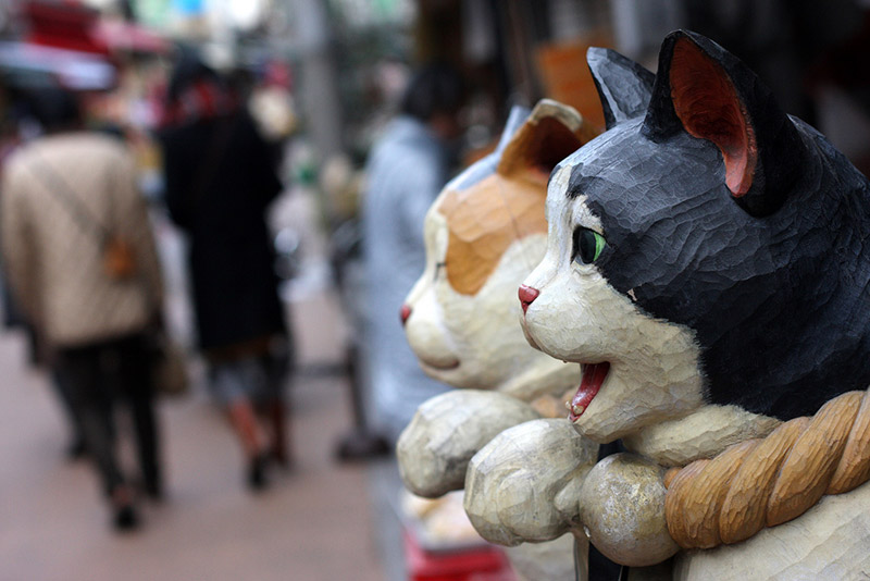 cat sculptures made of wood on a japanese street