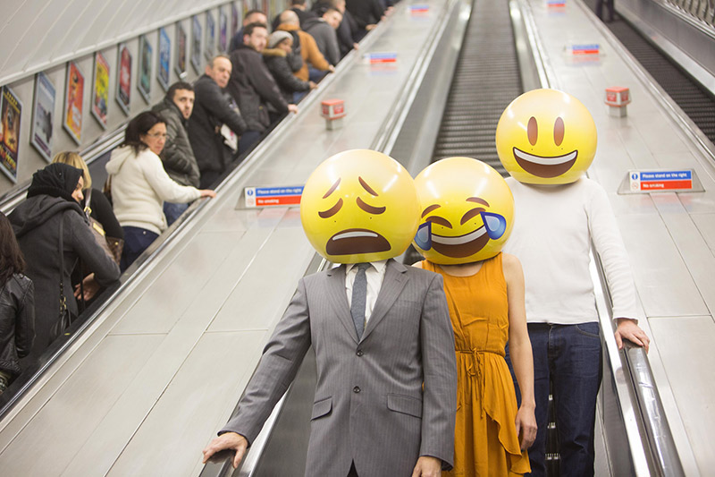people going down escalator with emoji masks