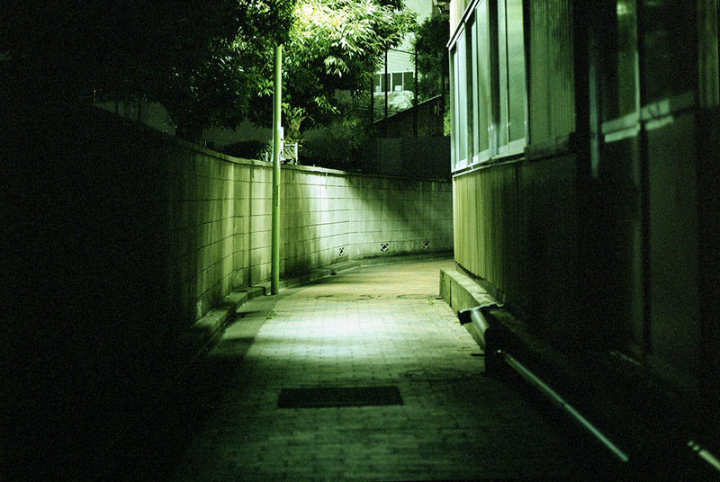 Empty alleyway in Japan illuminated by a single street lamp