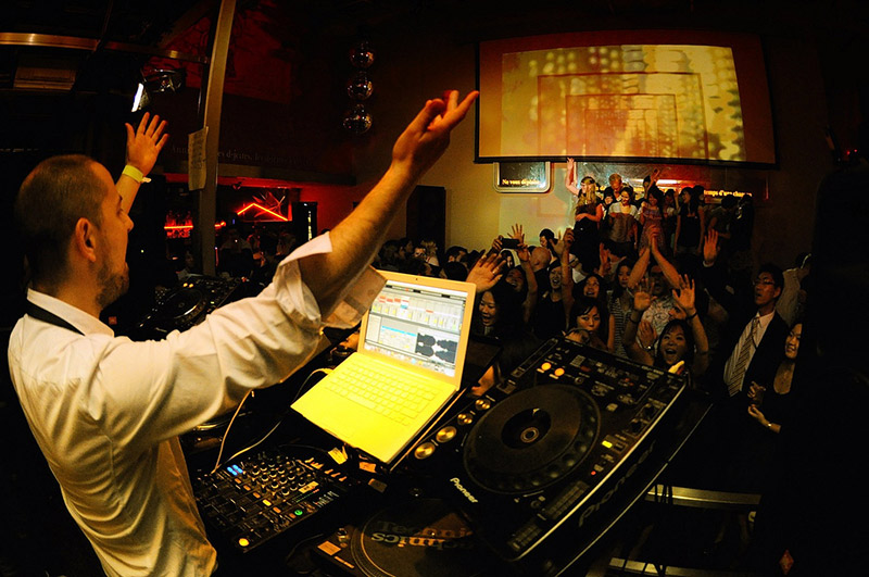 dj gesturing for partygoers to raise their hands