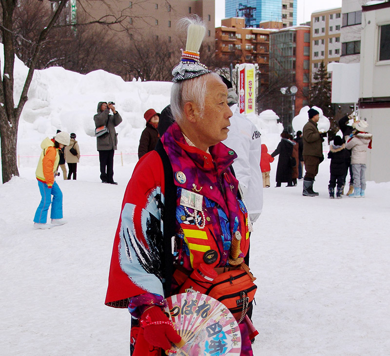 An eccentric Japanese man in colorful pants and jacket