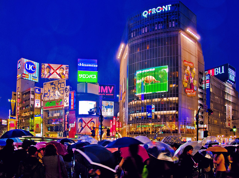 Pedestrians crossing the street during a rainy evening in Shibuya