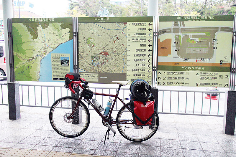 A bicycle in front of bulletin boards with a map
