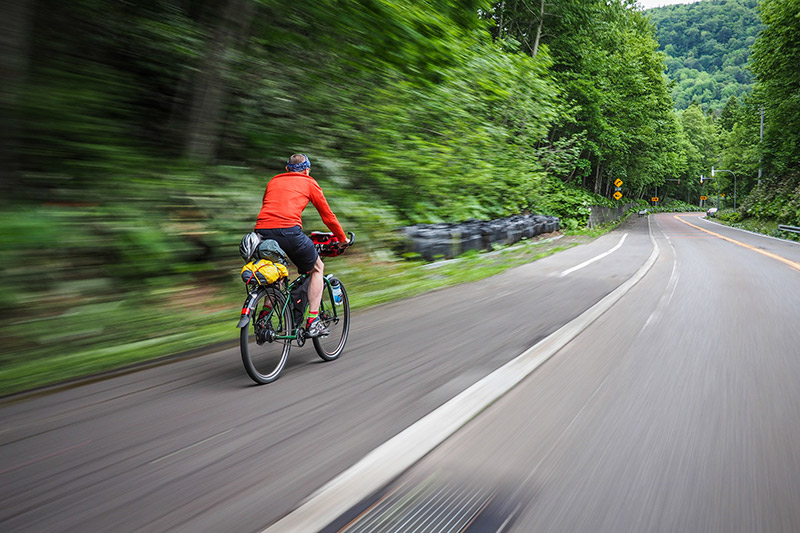 Man on his Japan Cycling Trip speeds down a road