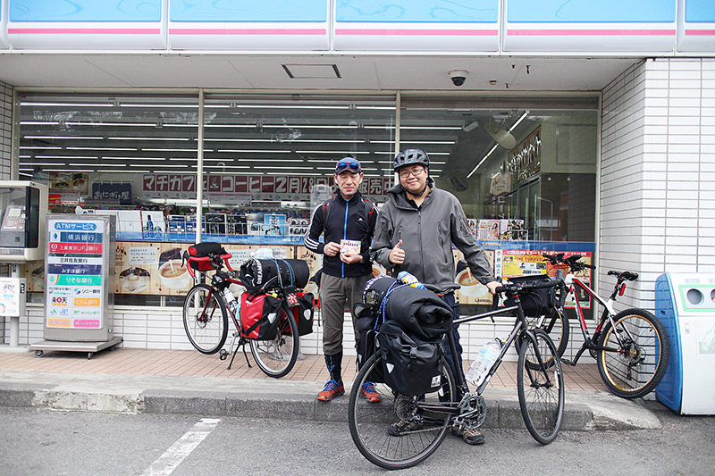 Men on a cycling trip in Japan take a break