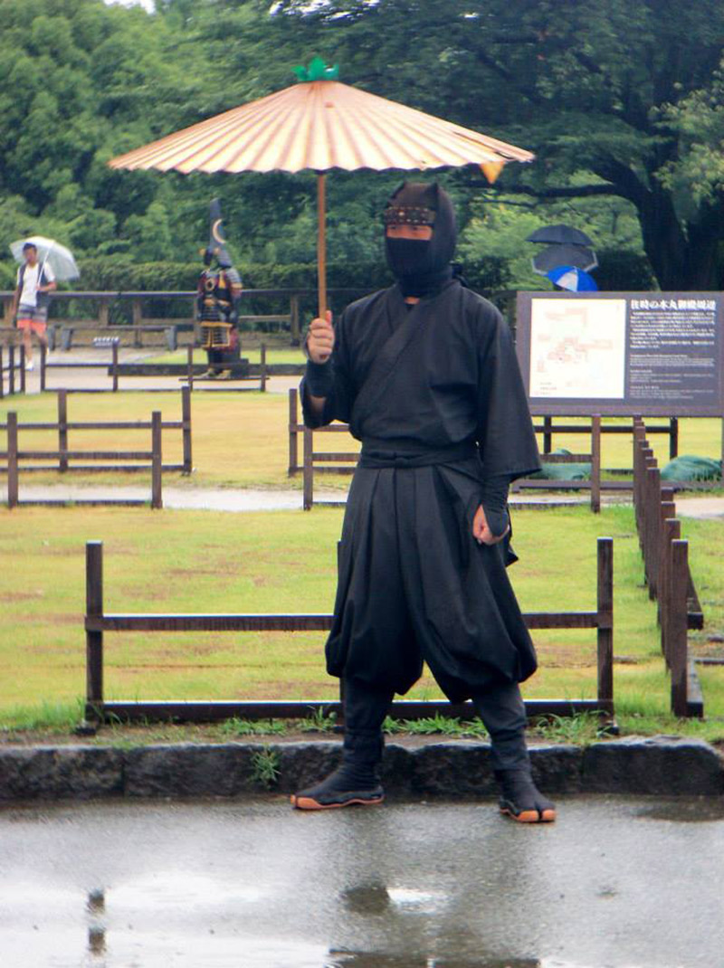 man in ninja costume standing in the rain