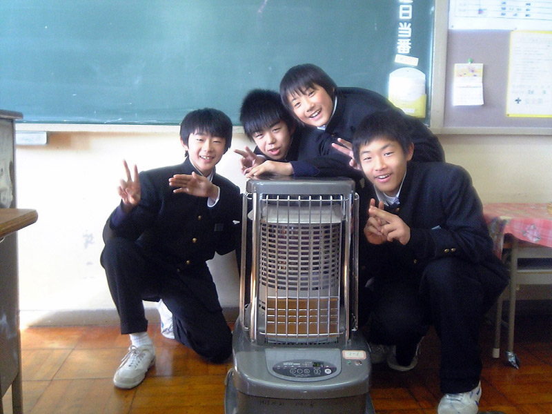 kids in front of a kerosene heater at a Japanese school