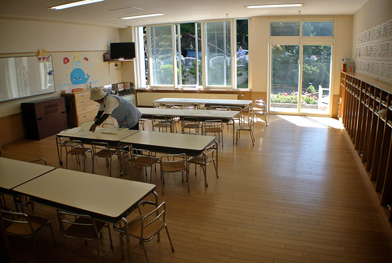 lady cleaning an empty japanese classroom