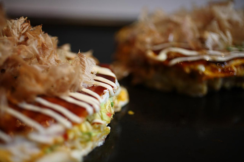 okonomiyaki on the griddle sizzling
