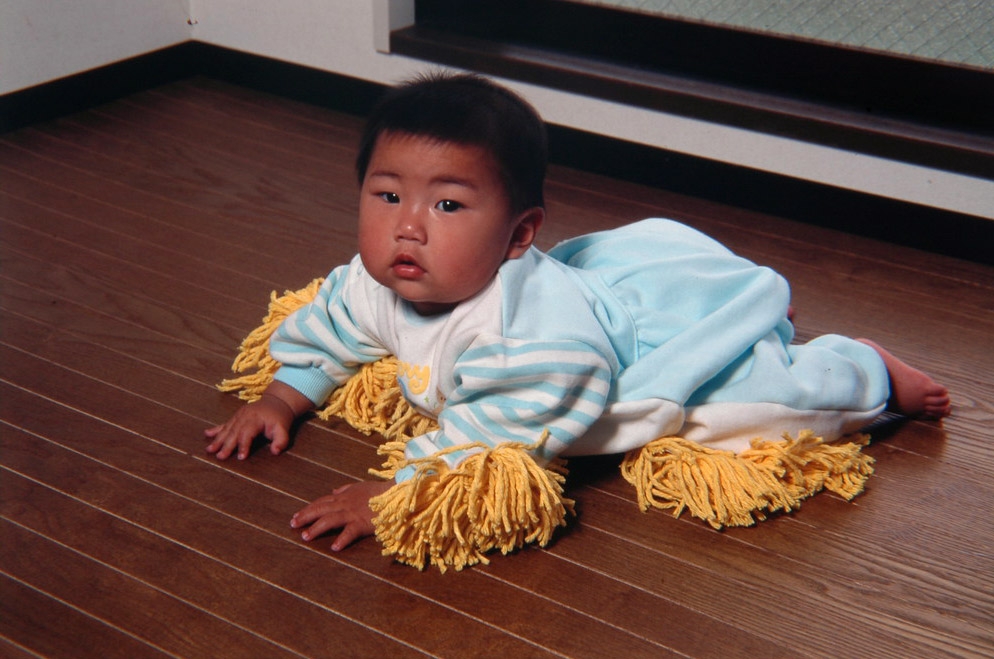 baby wearing suit with mop on it